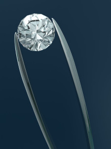 A diamond in a pair of tweezers. 3D render with HDRI lighting and raytraced textures.